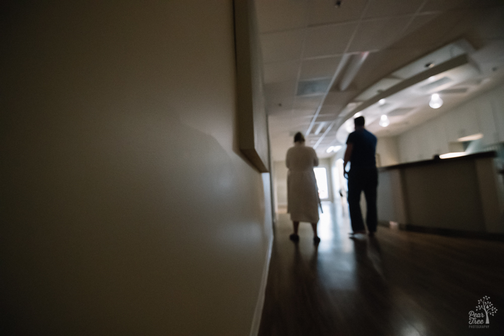 Pregnant mom walking with husband through Atlanta Birth Center lobby.