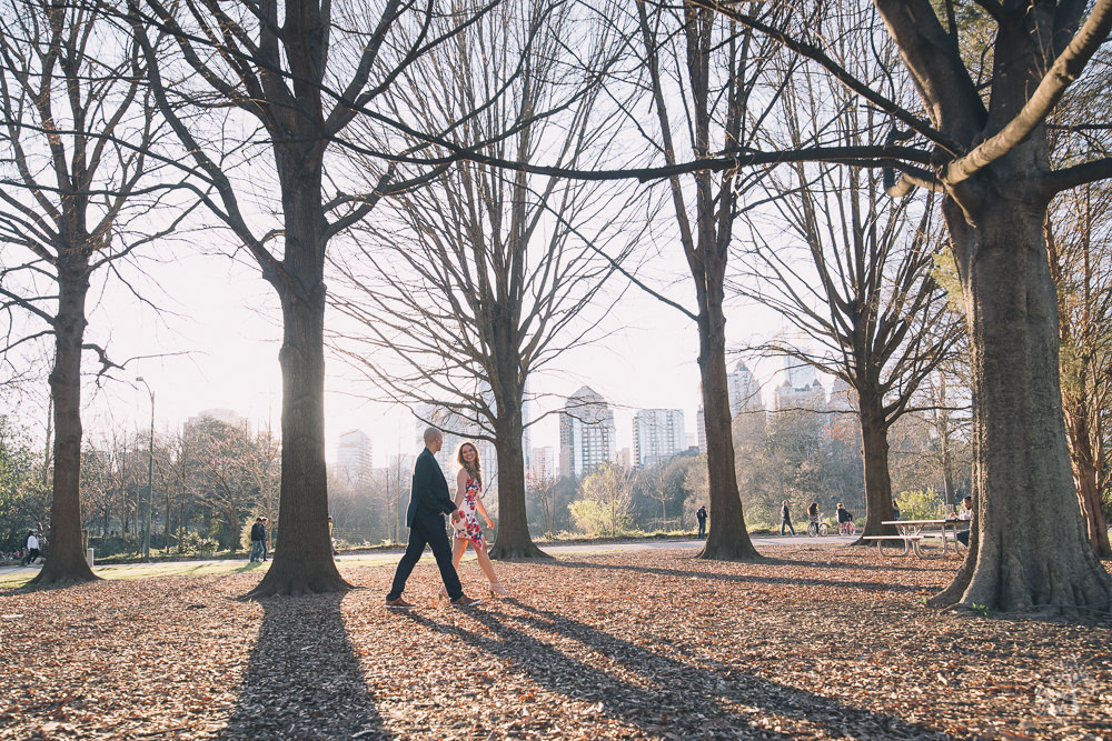 Engaged couple walking between tall trees at Piedmont Park with sun streaming down on them
