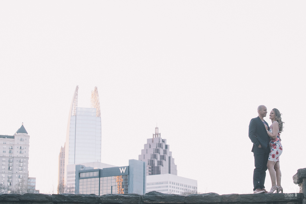 Engaged couple standing in Atlanta skyline at Piedmont Park.