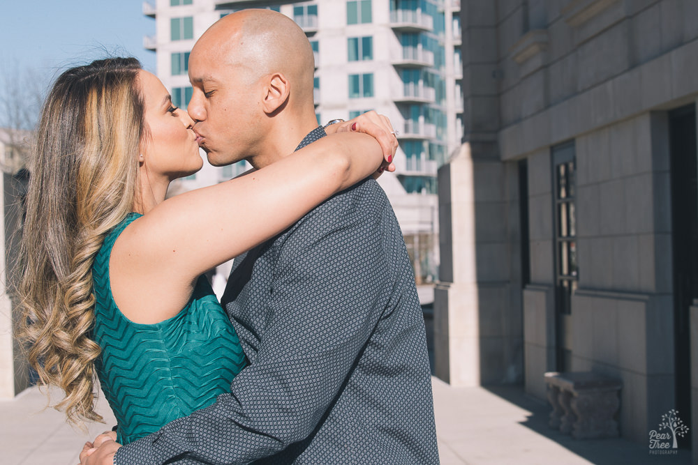 Fiances kissing each other in front of building with blue windows