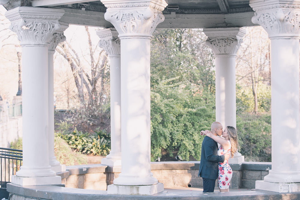 Engaged couple kissing in Piedmont Park gazebo