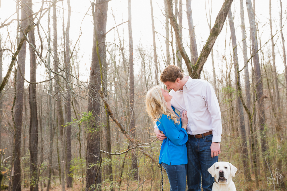 Engaged couple smiling at each other in the woods with yellow lab next to them