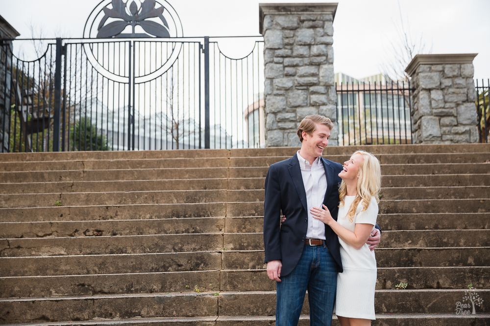 Engaged couple laughing in front of Atlanta Botanical Gardens gate