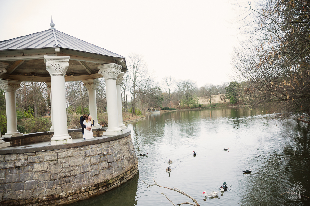 Engaged couple holding each other in Piedmont Park gazebo