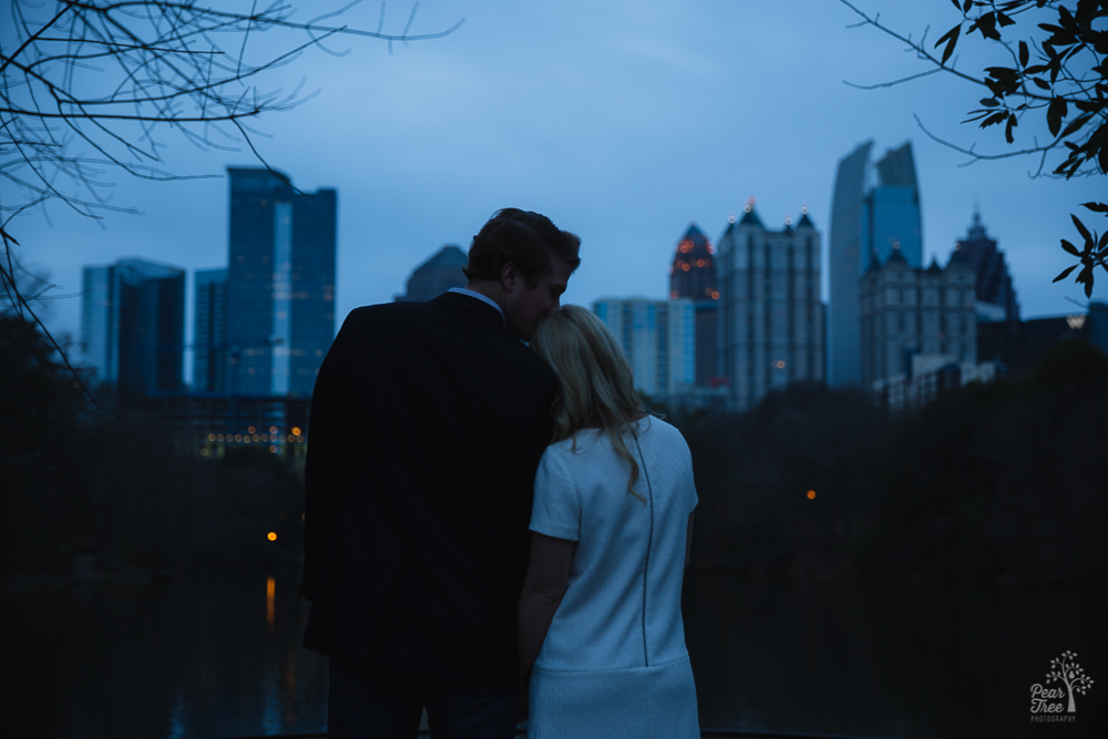 Engaged couple leaning into each other in the dark of Atlanta