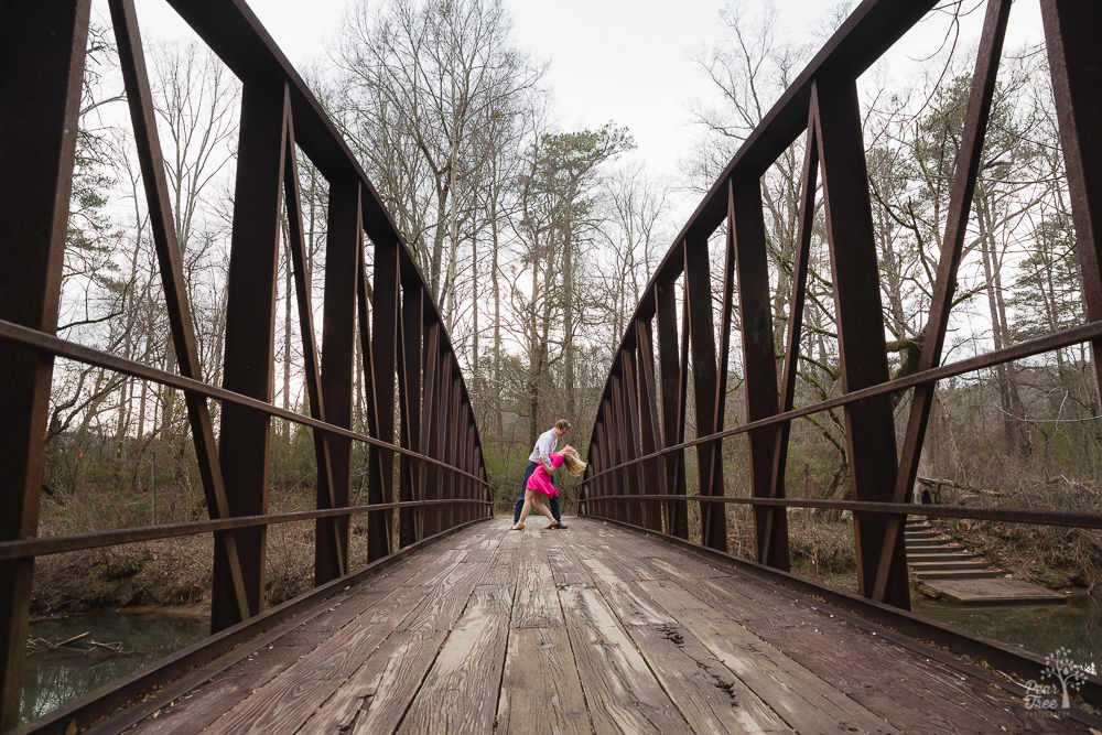 Engaged couple dancing on old Chattahoochee River bridge