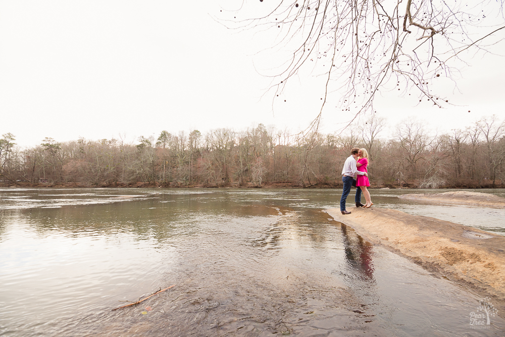 Engaged couple kissing on the shoals of the Chattahoochee River