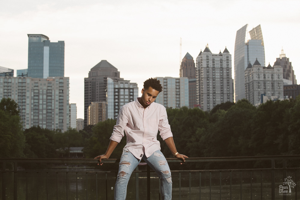 High school senior boy sitting on railing and looking down in front of Atlanta skyline and Lake Clara Meade