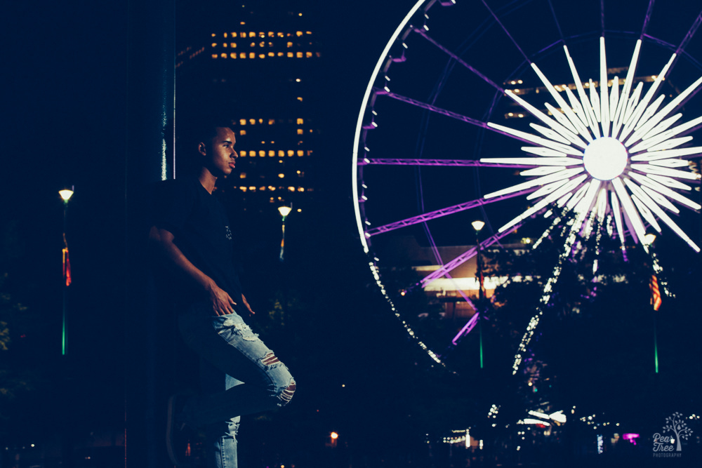 African American teenage boy standing in front of Atlanta ferris wheel at night
