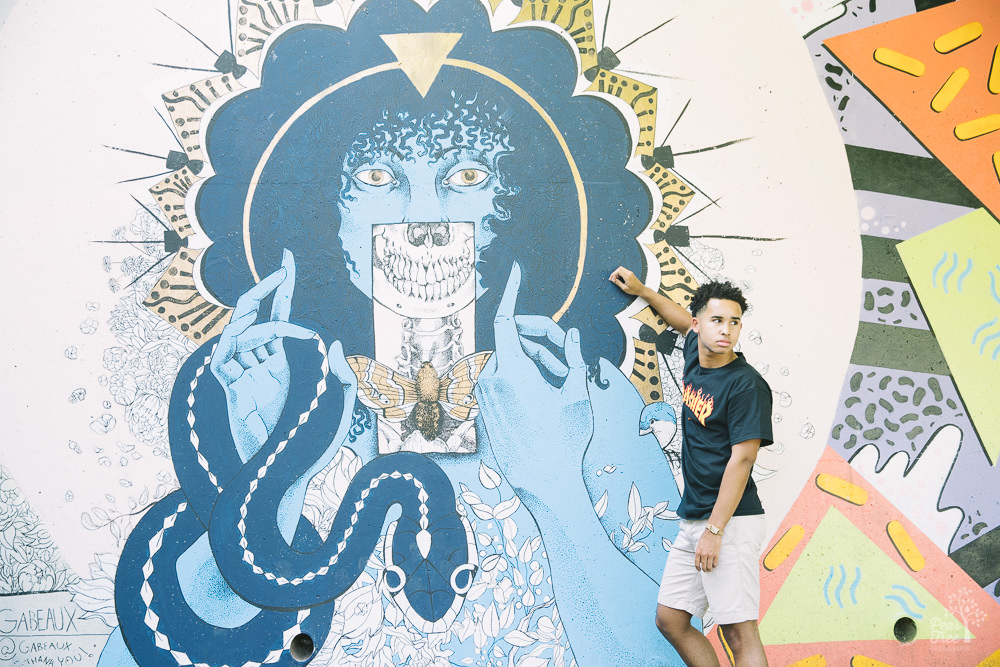 African American teenage boy standing in front of Atlanta mural