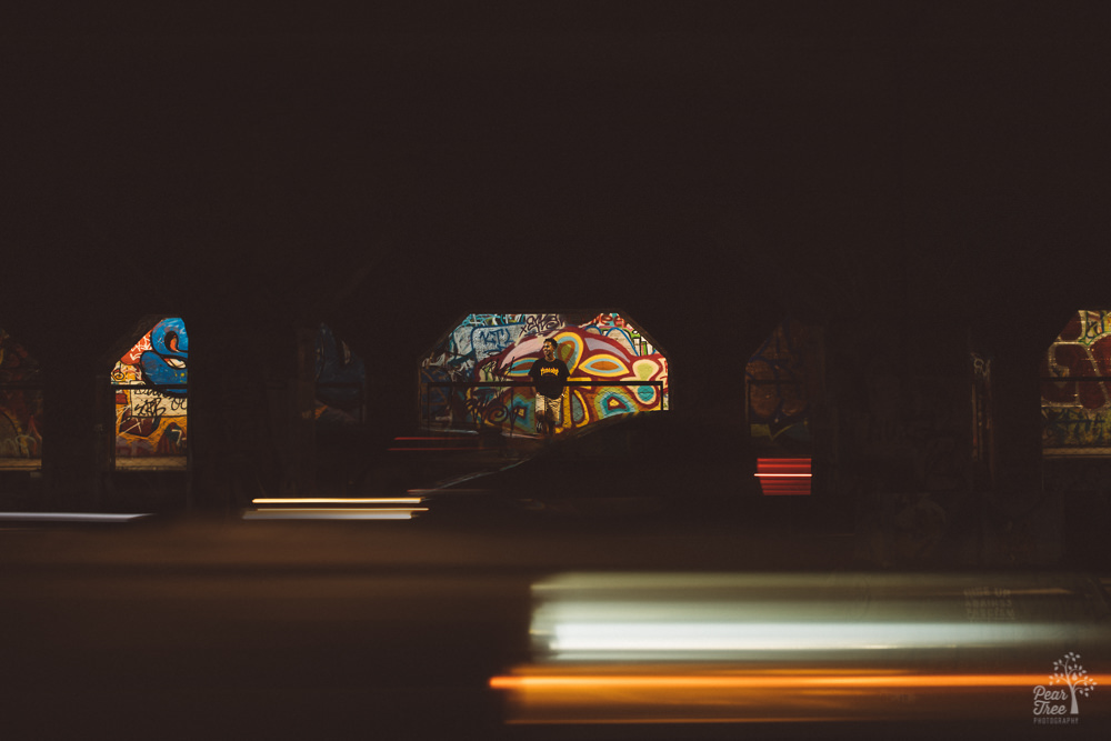 African American teenager standing in Krog Street tunnel with light trails of cars moving in front of him