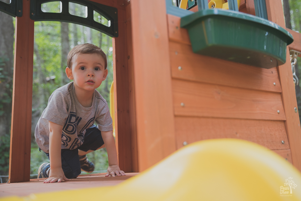 Three year old boy in play set