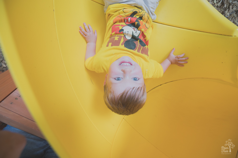 Three year old boy coming out of slide and smiling