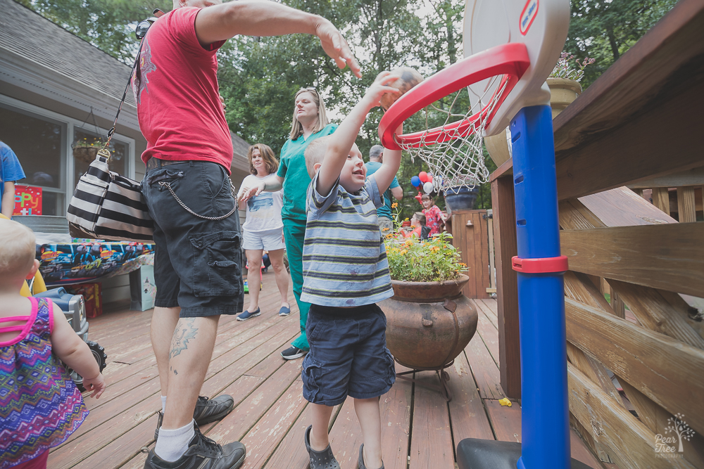 Three year old boy dunking a basket ball