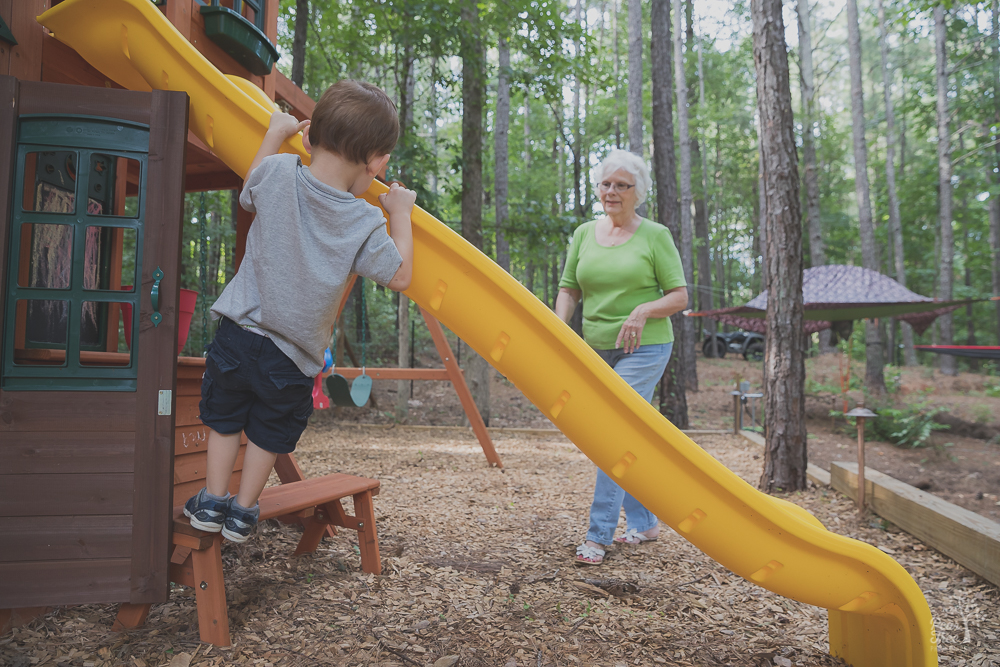 Three year old boy hanging on slide while grandmother watches