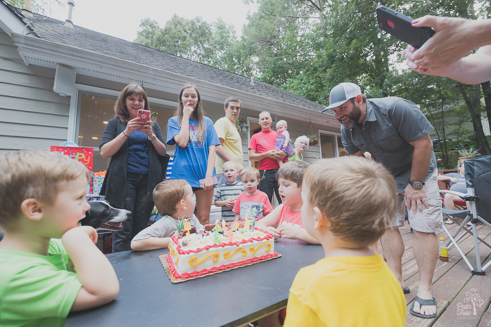 Three year old birthday boy with cake surrounded by family and friends