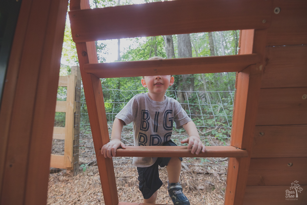 Three year old boy climbing up playset ladder