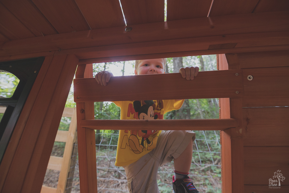 Three year old boy climbing up playset ladder and smiling