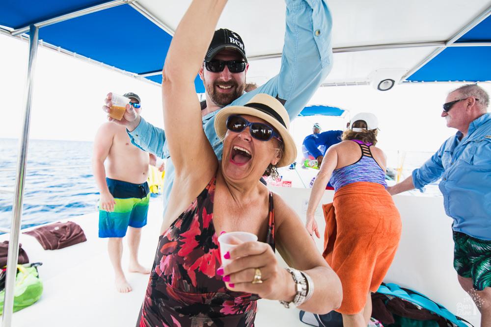 Woman dancing on catamaran with drink in hand