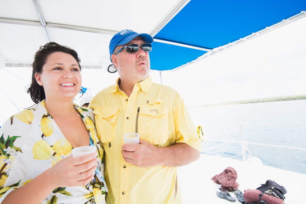 Father and daughter standing close while looking out on a catamaran.