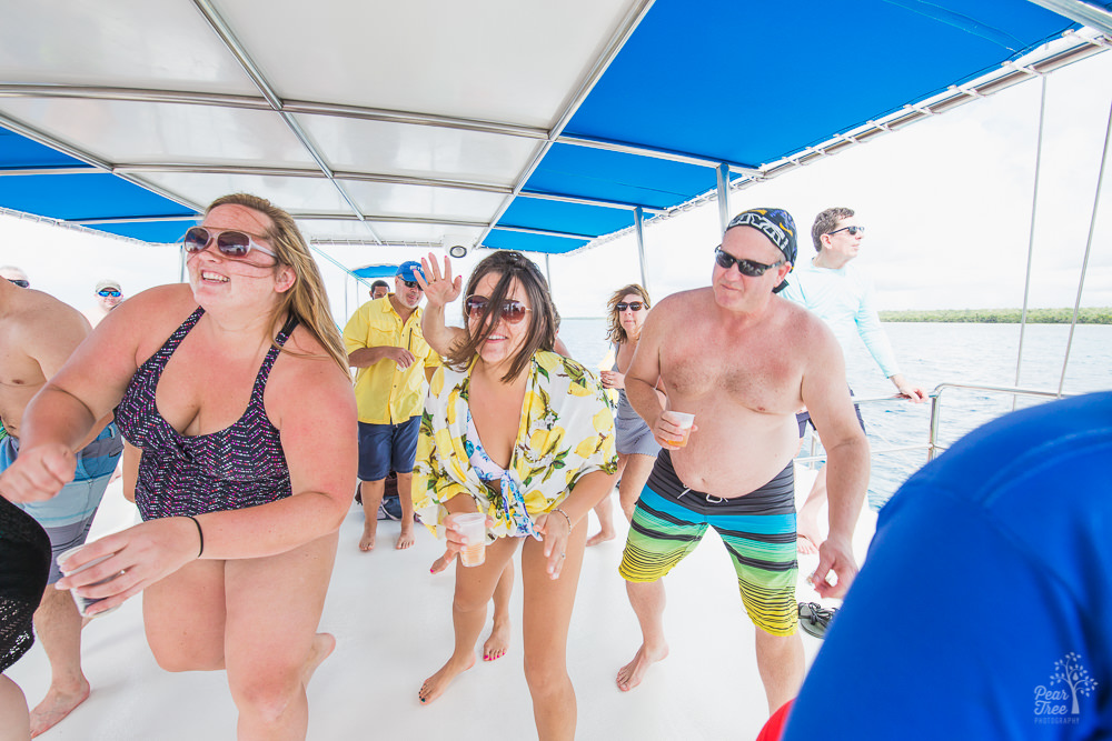 People line dancing with drinks in hand on a catamaran