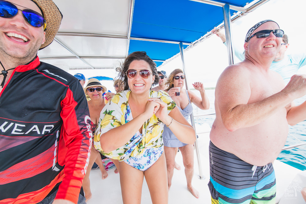People dancing and laughing on a catamaran