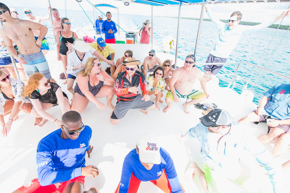People getting down low while dancing on a catamaran