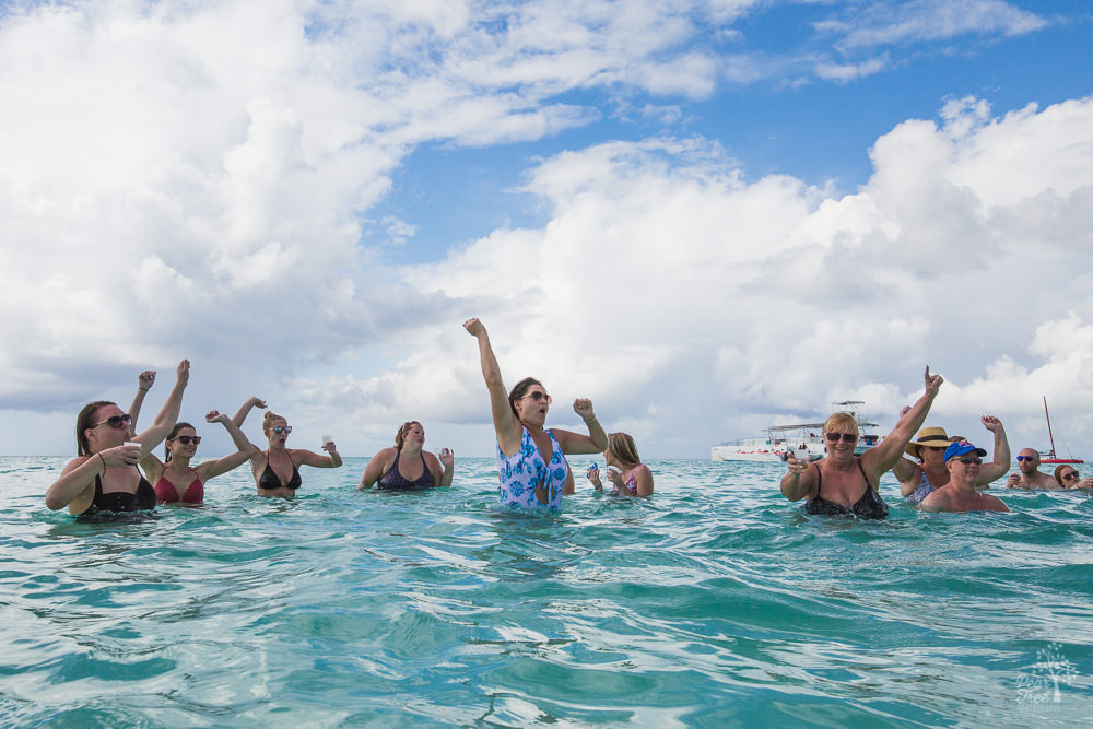 People dancing in the Caribbean Sea with hands over their heads
