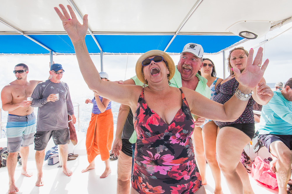 Woman dancing with hands up while shouting and happy onlookers on the catamaran