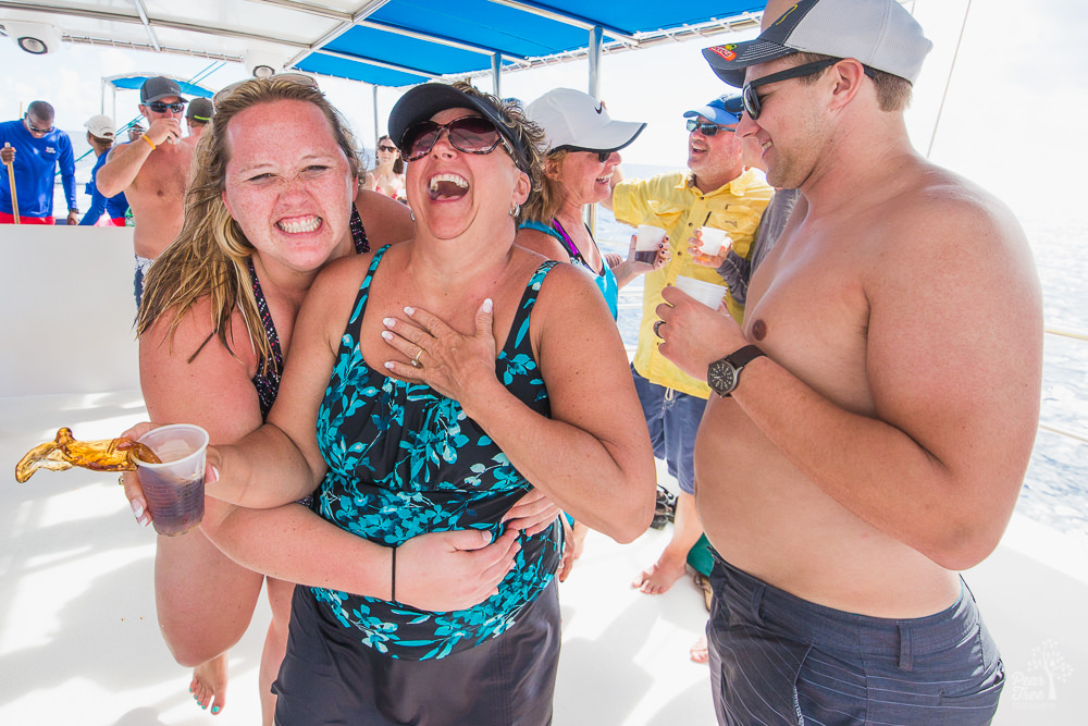 Women hugging and laughing on a catamaran while a drink spills