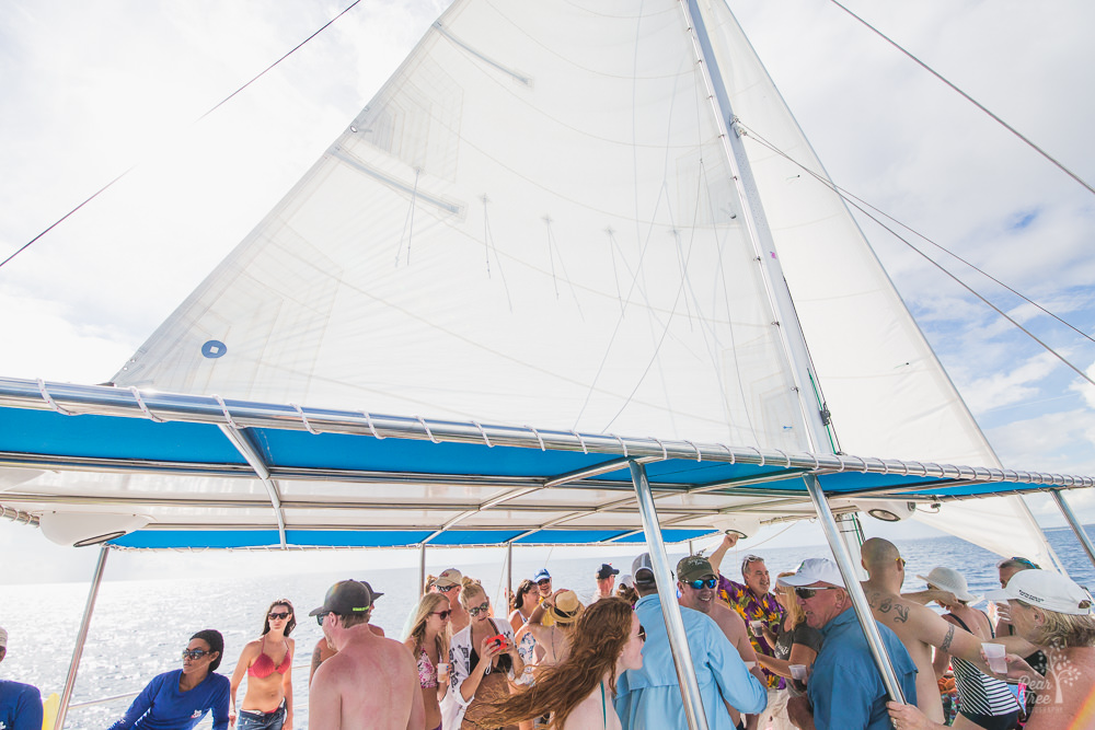 Catamaran sail over a deck filled with people dancing on the Caribbean Sea
