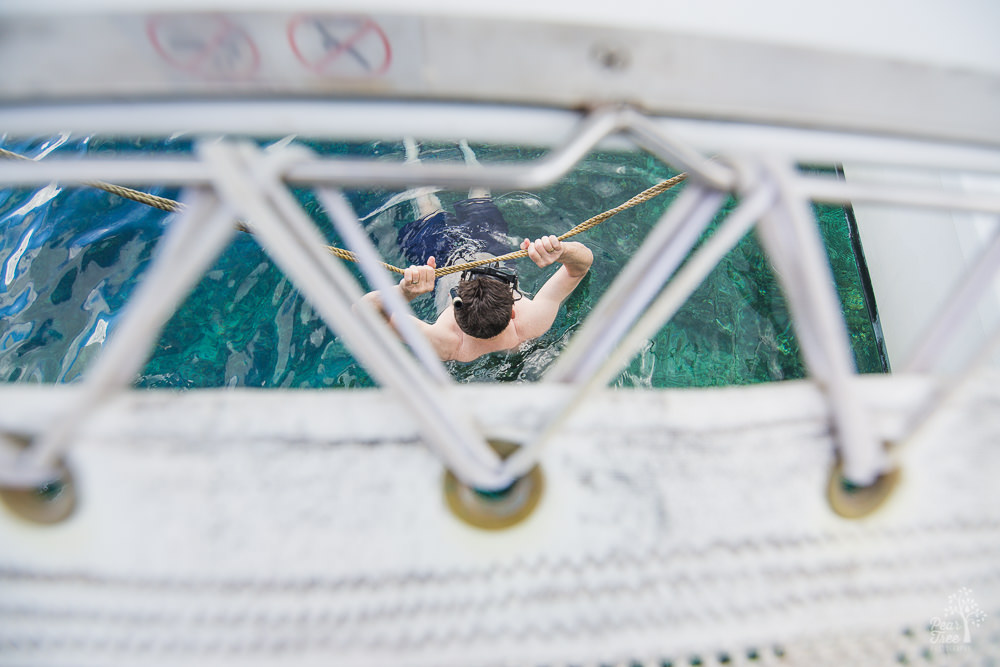 Looking down through catamaran netting to see man hanging onto rope in the water