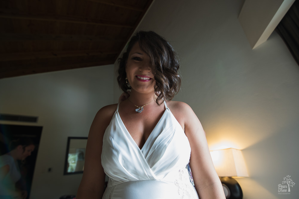 Bride smiling while necklace is clasped behind her back