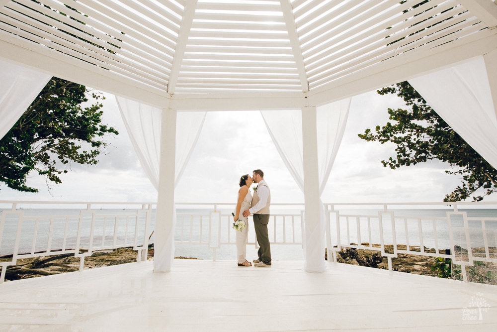 Wedding couple kissing in a Dominican gazebo and the sea behind them