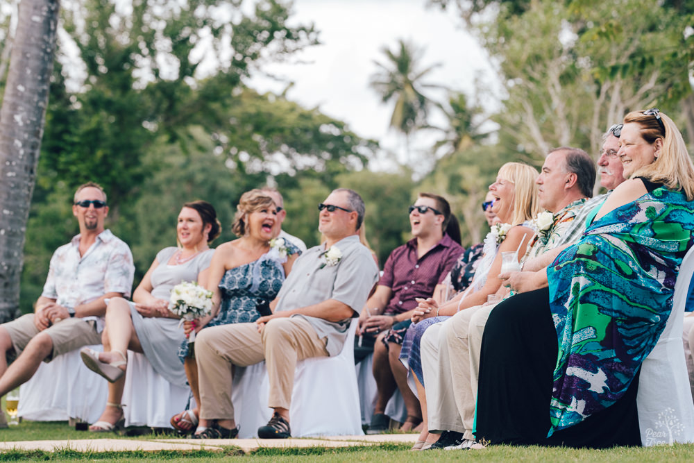 Family laughing in front row during wedding ceremony