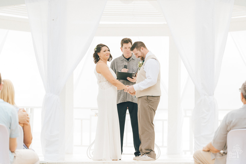 Wedding couple laughing during ceremony while holding hands