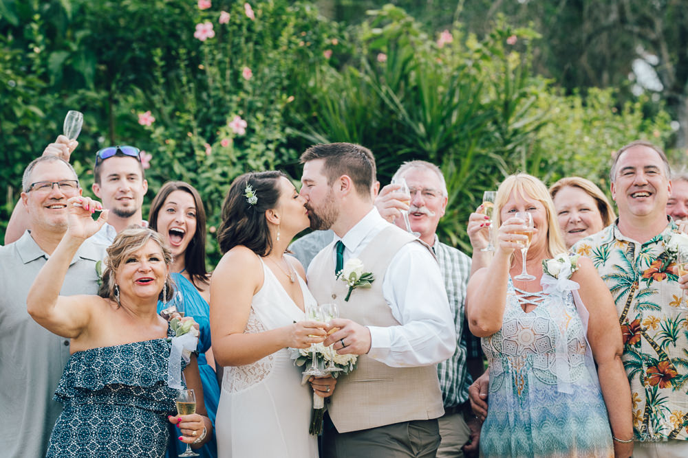 Bride and groom kissing while surrounded by cheering family and friends