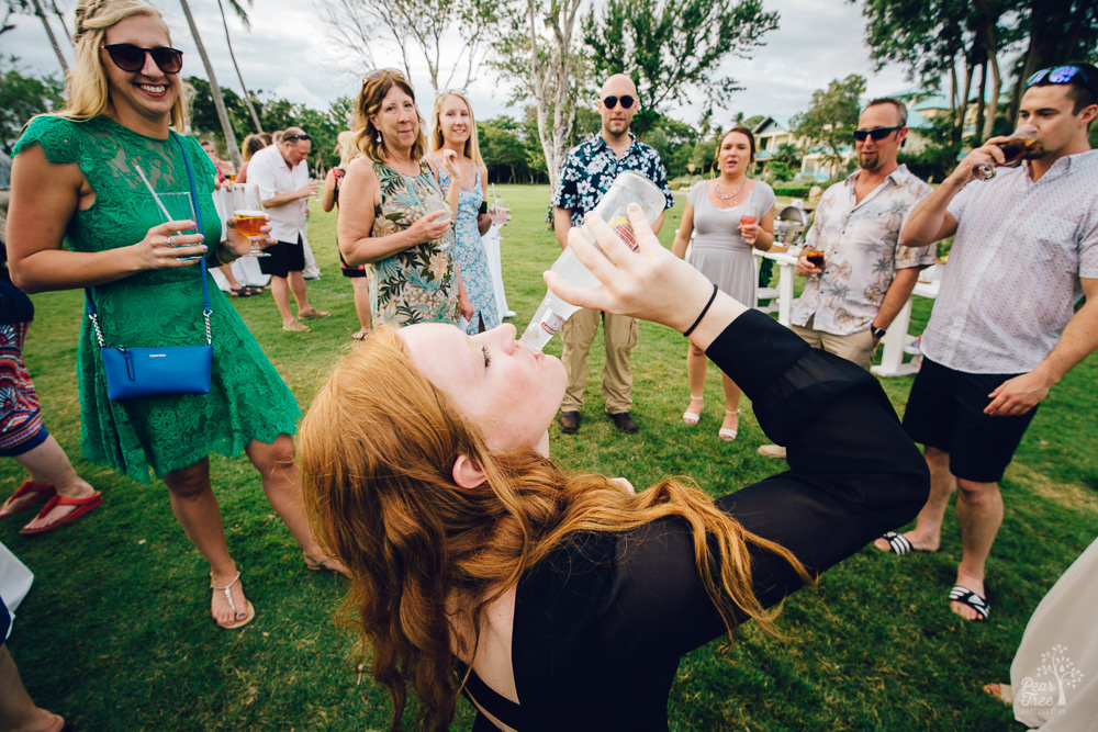 Red head wedding guest kneeling while drinking a Smirnoff Ice in one go