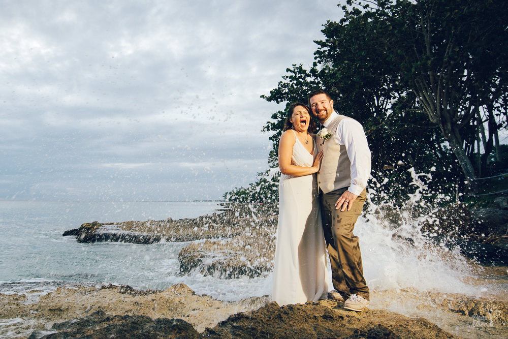 Bride and groom getting massively splashed while standing on Dominican Republic beach rocks