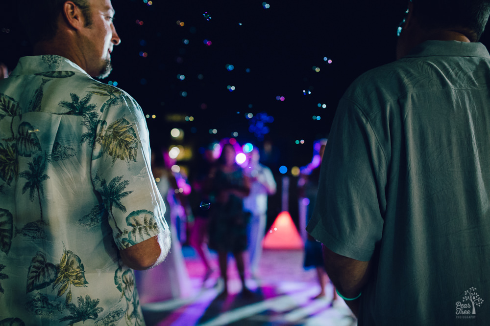 Wedding guests on dance floor surrounded by bubbles