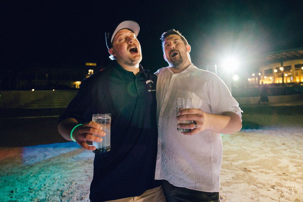 Groom singing with a friend while holding drinks at wedding reception