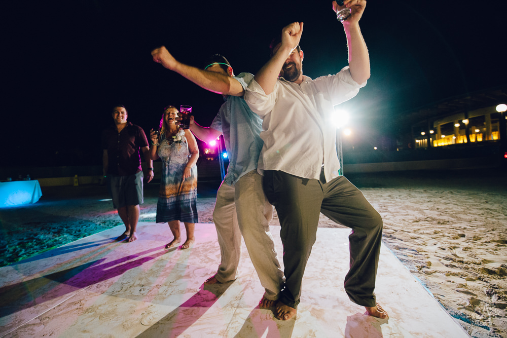 Groom dancing and hip bumping with friend on wedding dance floor