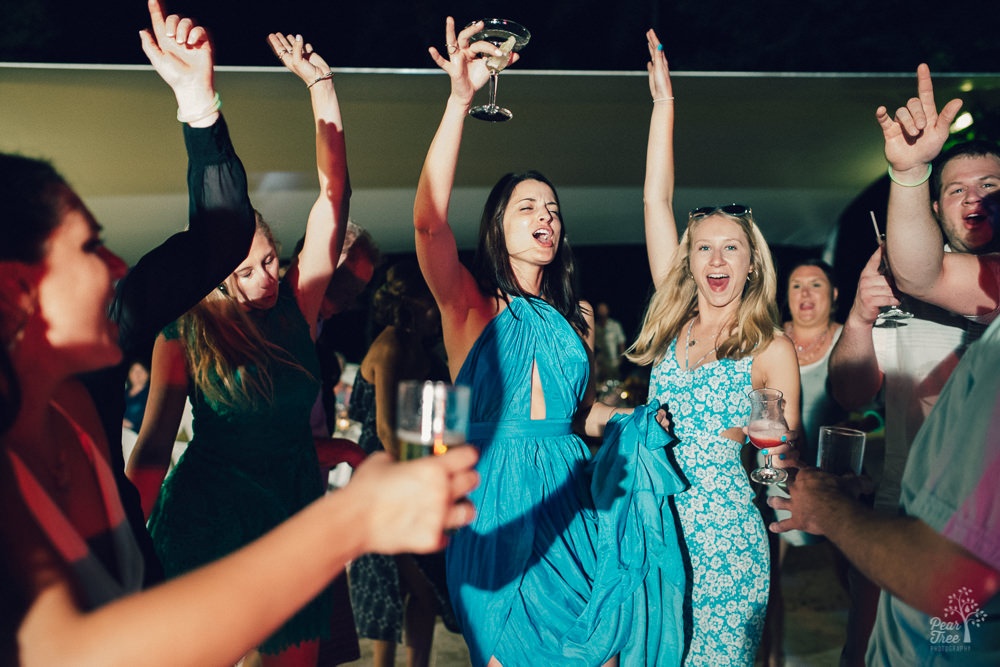 Women dancing and celebrating with drinks raised while singing at wedding reception