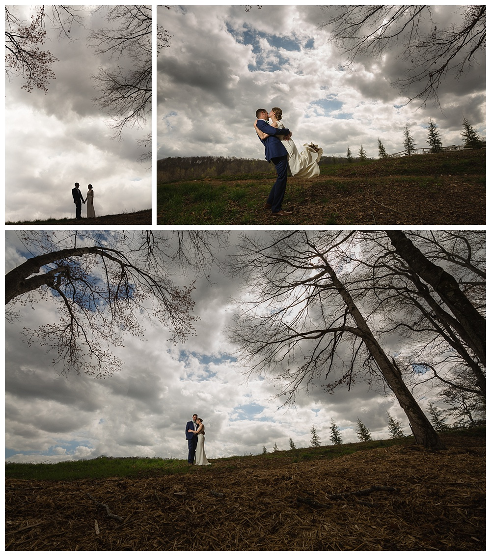 Bride and groom on hill with dramatic skies.