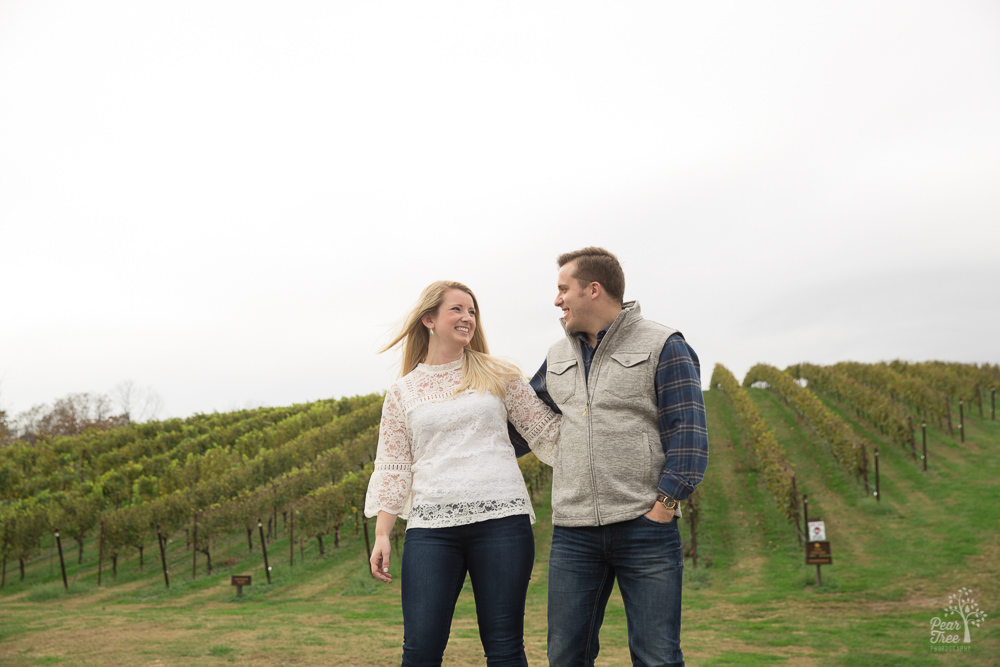 Engaged couple smiling at each other in front of vineyard rows of grapes