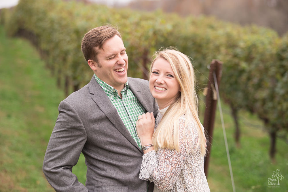 Engaged couple laughing in front of vineyard rows