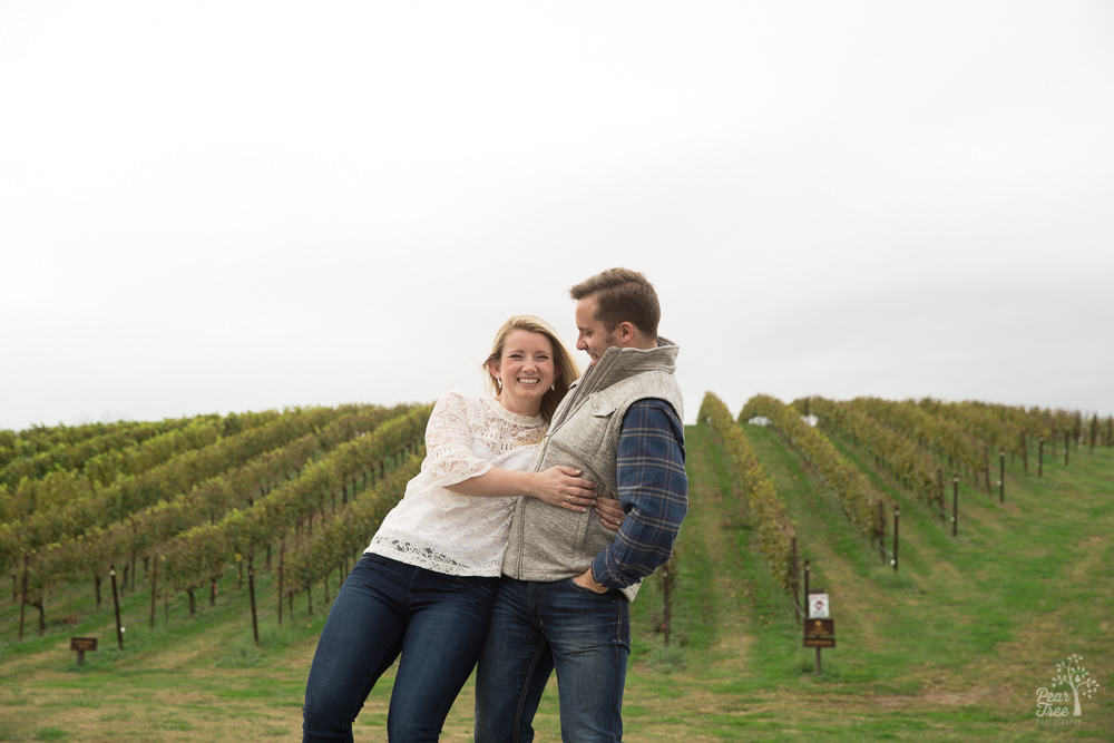 Handsome man catching his fiance as she starts to fall in a vineyard