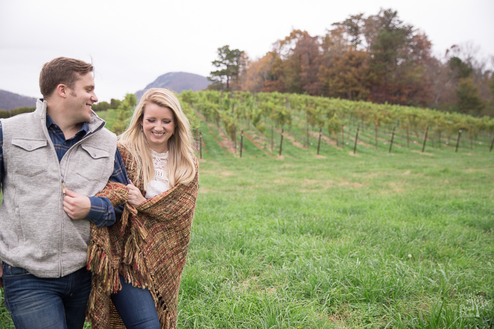 Engaged couple walking through Yonah Mountain Vineyard with blanket wrapped around them