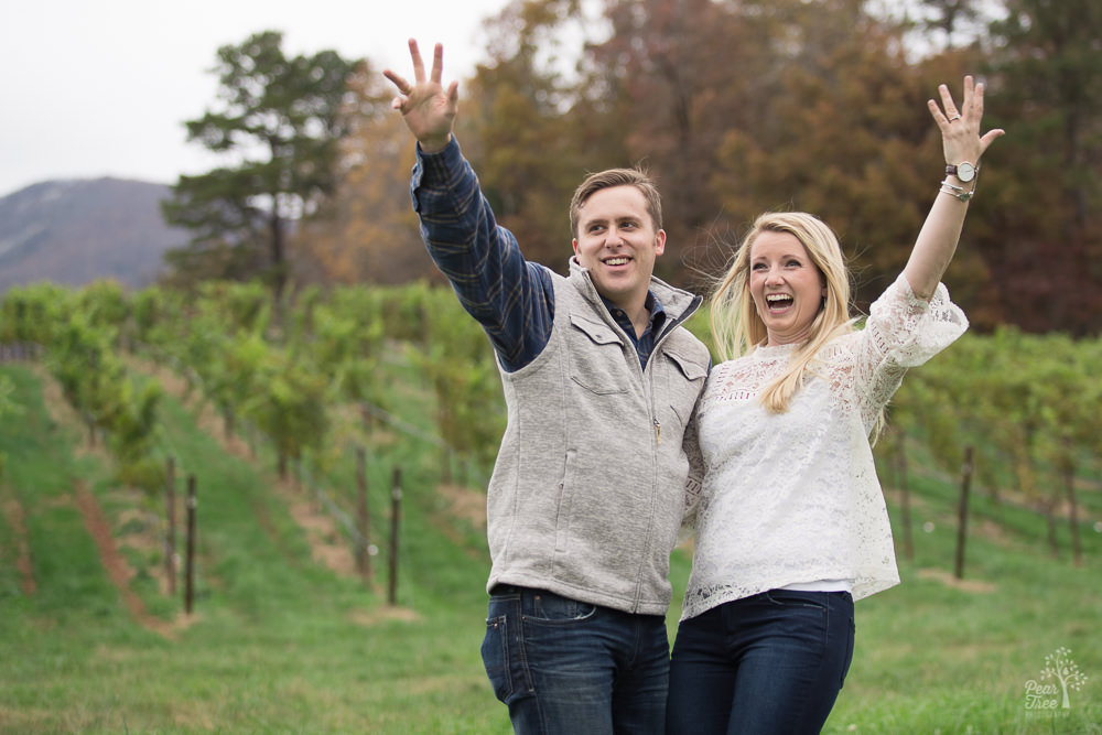 Engaged couple waving and holding up their hands while smiling
