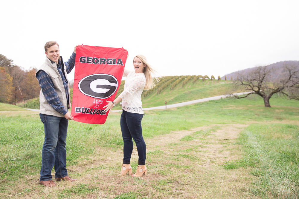 Engaged couple holding up UGA flag in excitement